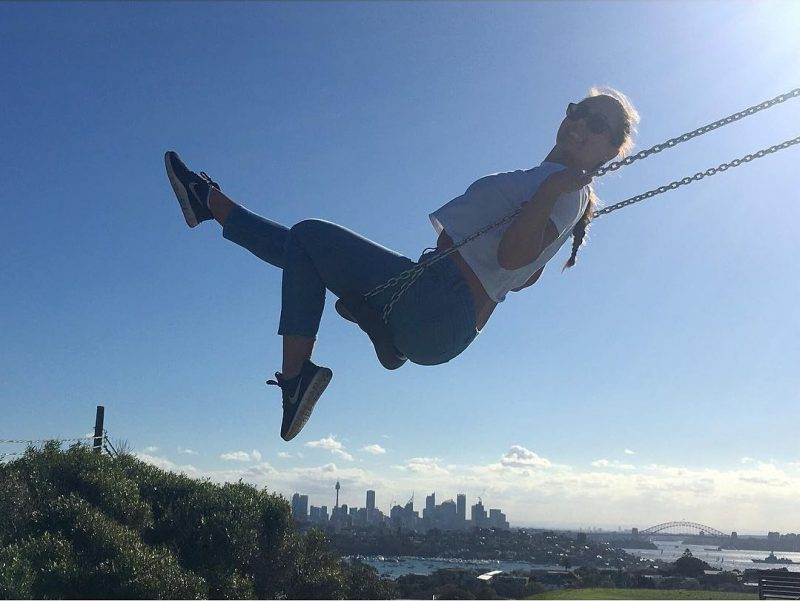 Girl on swing, city backdrop